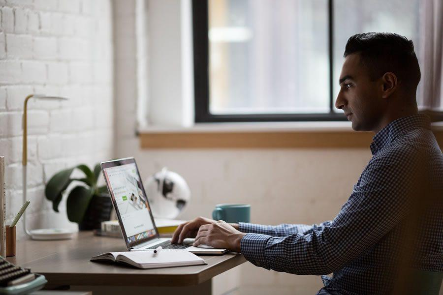 homem trabalhando em home office, digita no computador