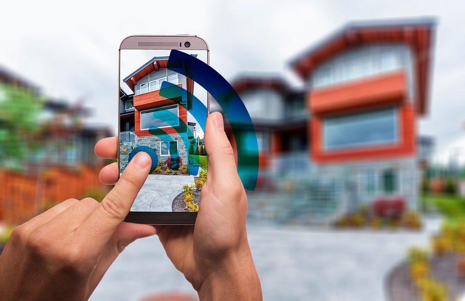 Foto ilustrativa de aparelho celular conectando e enviando comando digital em direção a uma residência - Imagem: Pixabay