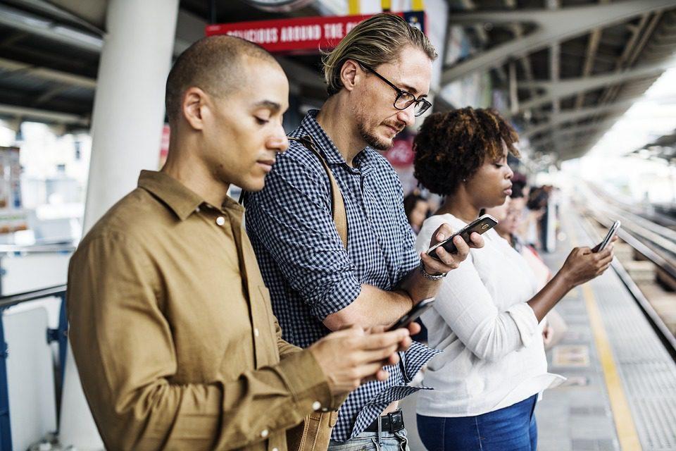 três pessoas em uma fila, com olhos voltados para os seus smartphones - foto pixabay