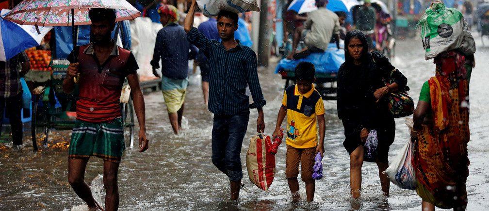 As pessoas andam sobre a água enquanto as estradas são inundadas devido a fortes chuvas em Dhaka, Bangladesh, em 26 de julho de 2017.Imagem: REUTERS / Mohammad Ponir Hossain