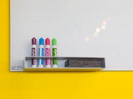 quadro branco com canetas para escrita.
