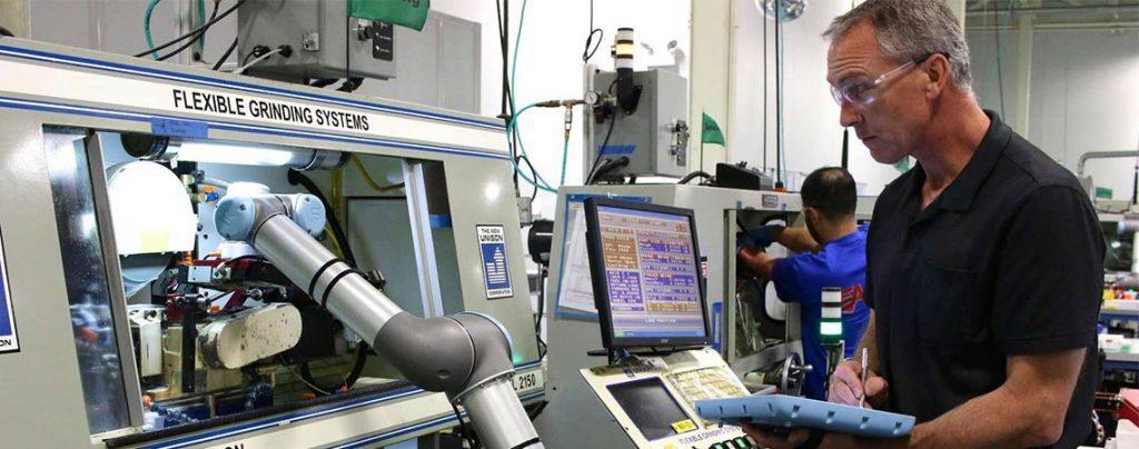 Foto mostra trabalhador produzindo com o apoio de robôs colaborativos.