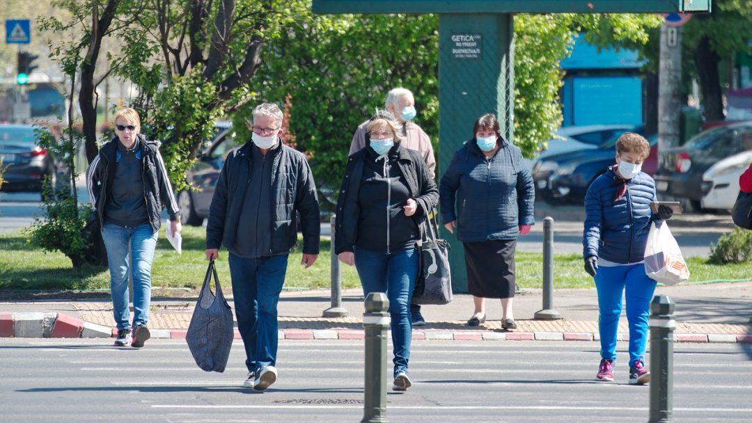 A pandemia, por meio de bloqueios e outras restrições de movimento, mudou o fluxo das cidades quase da noite para o dia, e introduziu novas variáveis para projetos de mobilidade. Foto: Pixabay - pessoas de máscara atravessando a rua.