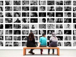 tres pessoas sentadas diante de uma grande tela onde aparecem dezenas de rostos