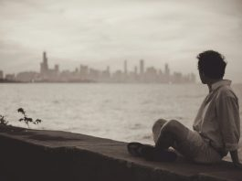 Homem olhando a paisagem de uma cidade, à beira de uma mureta foto: Pixabay