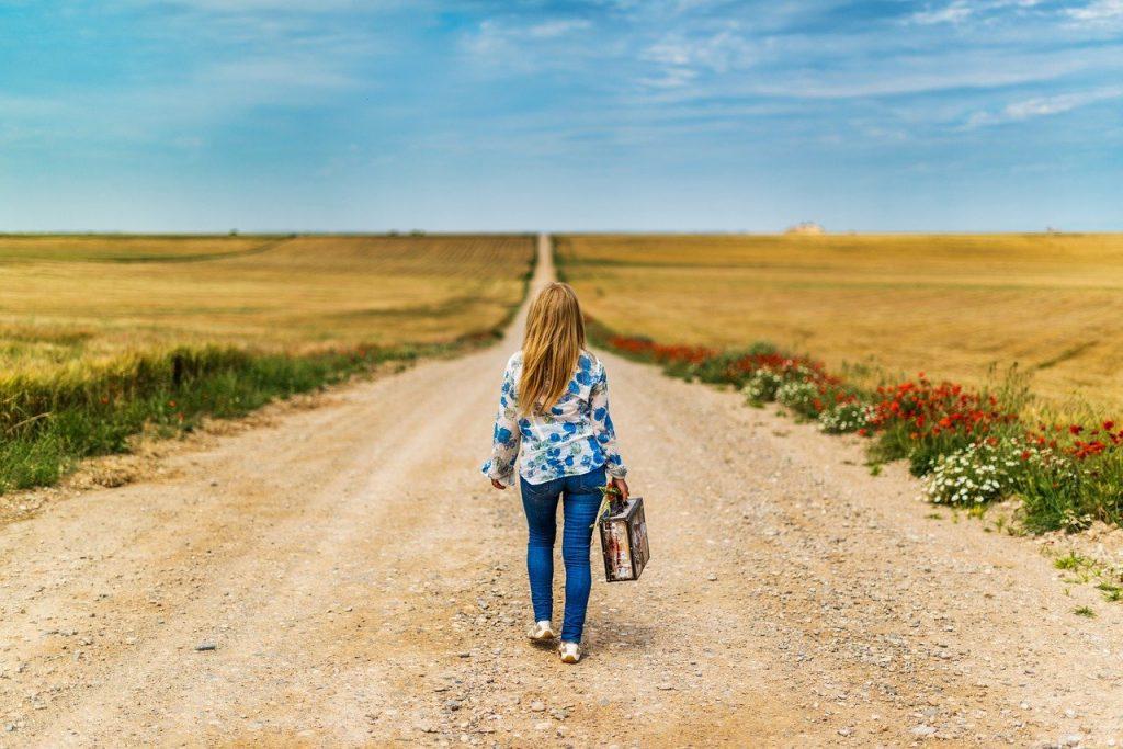 jovem andando por estrada de terra com uma mala