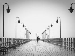 casal passeia em um pier em dia chuvoso