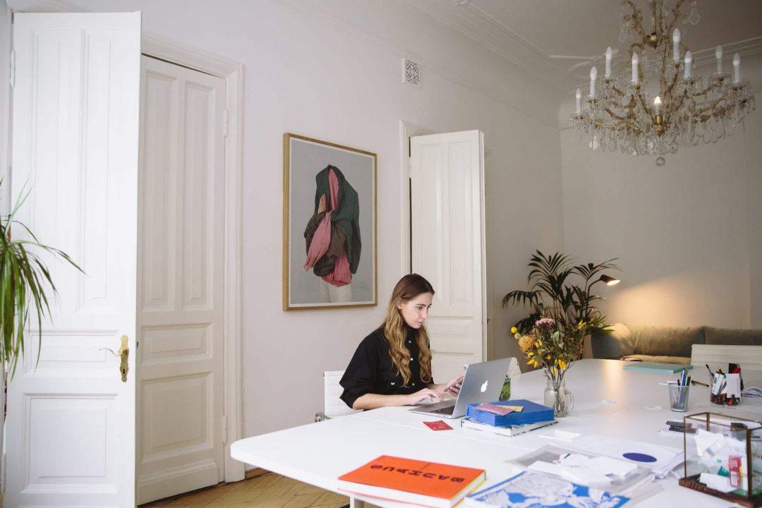 photo of woman sitting near wooden doors