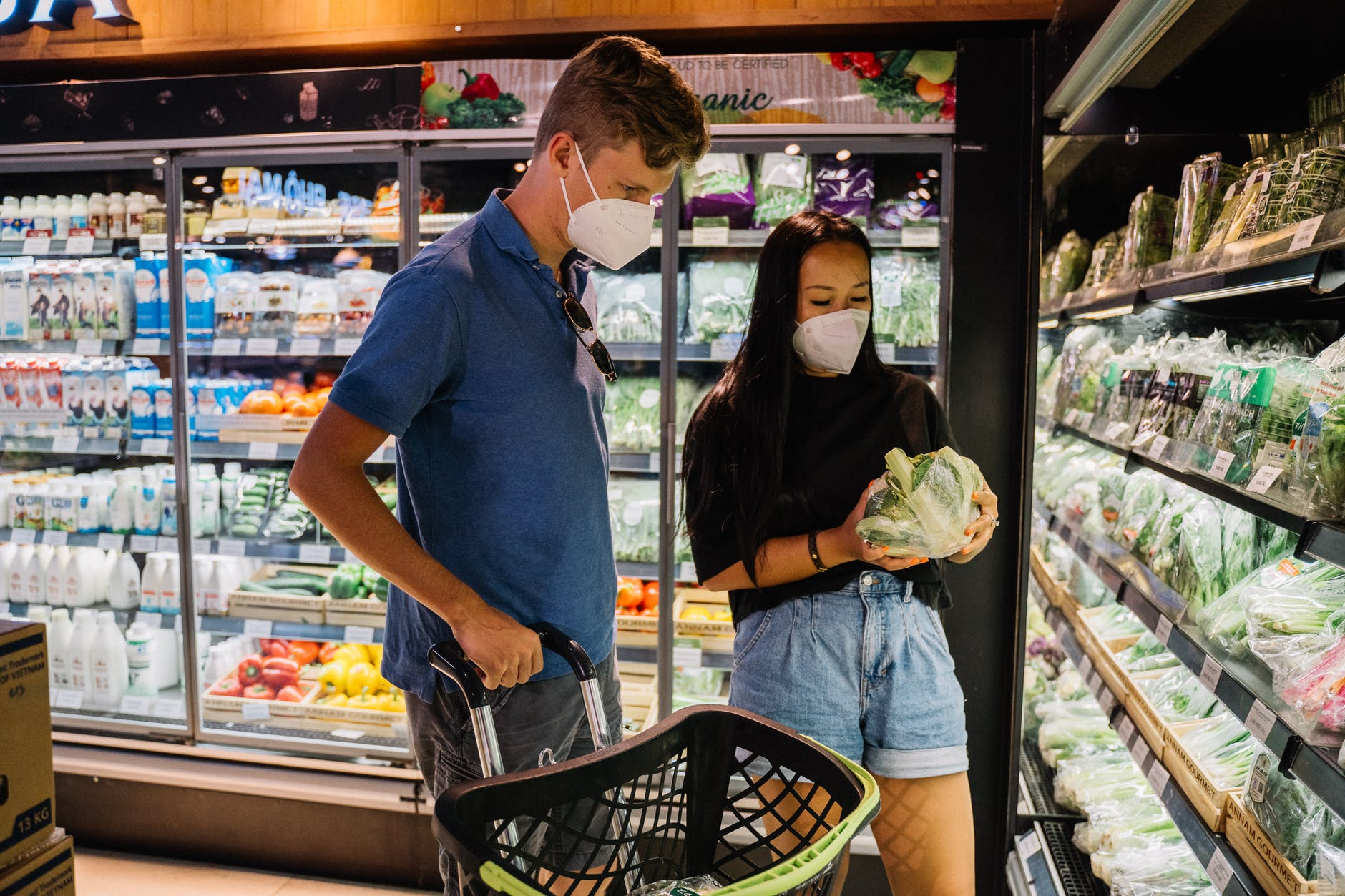 a couple buying vegetable inside a grocery store