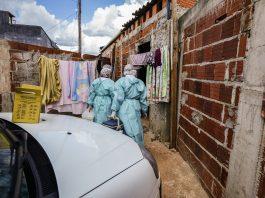 equipe de vacinação, com roupa de proteção, entra em favela Foto: Breno Esaki/Agência Saúde