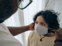 profissional de saúde ajuda paciente a colocar máscara. Foto: Pexels
