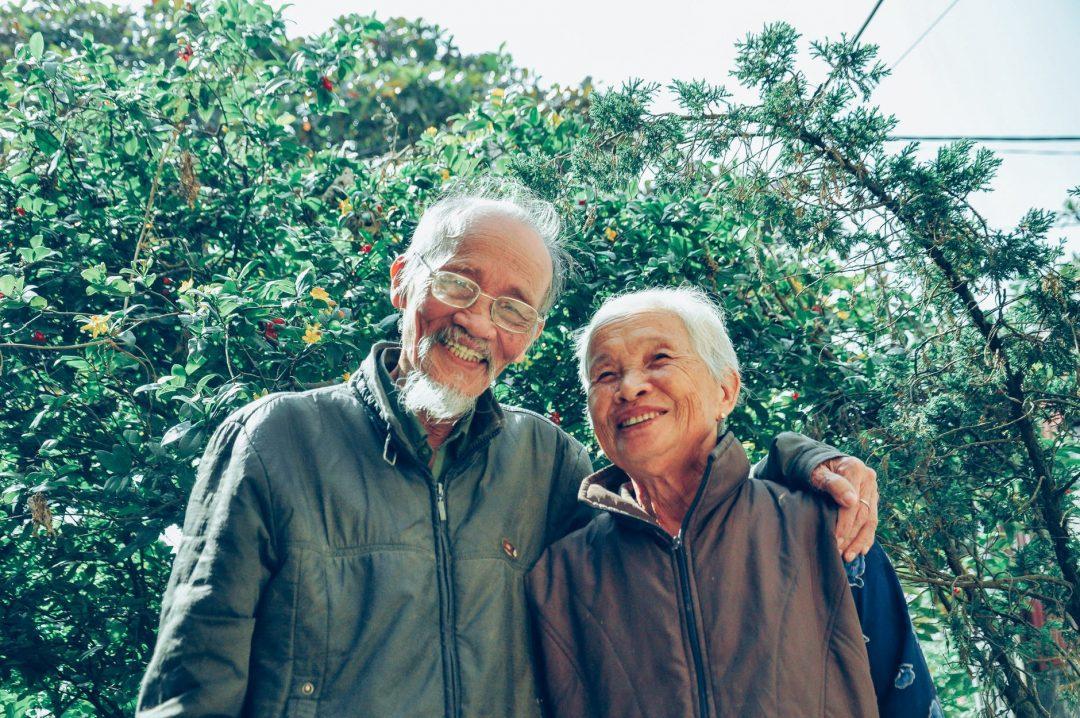smiling man and woman wearing jackets casal de idosos sorridentes - Conheça mais sobre a gerontologia, profissão do futuro que aborda o processo de crescente envelhecimento das populações