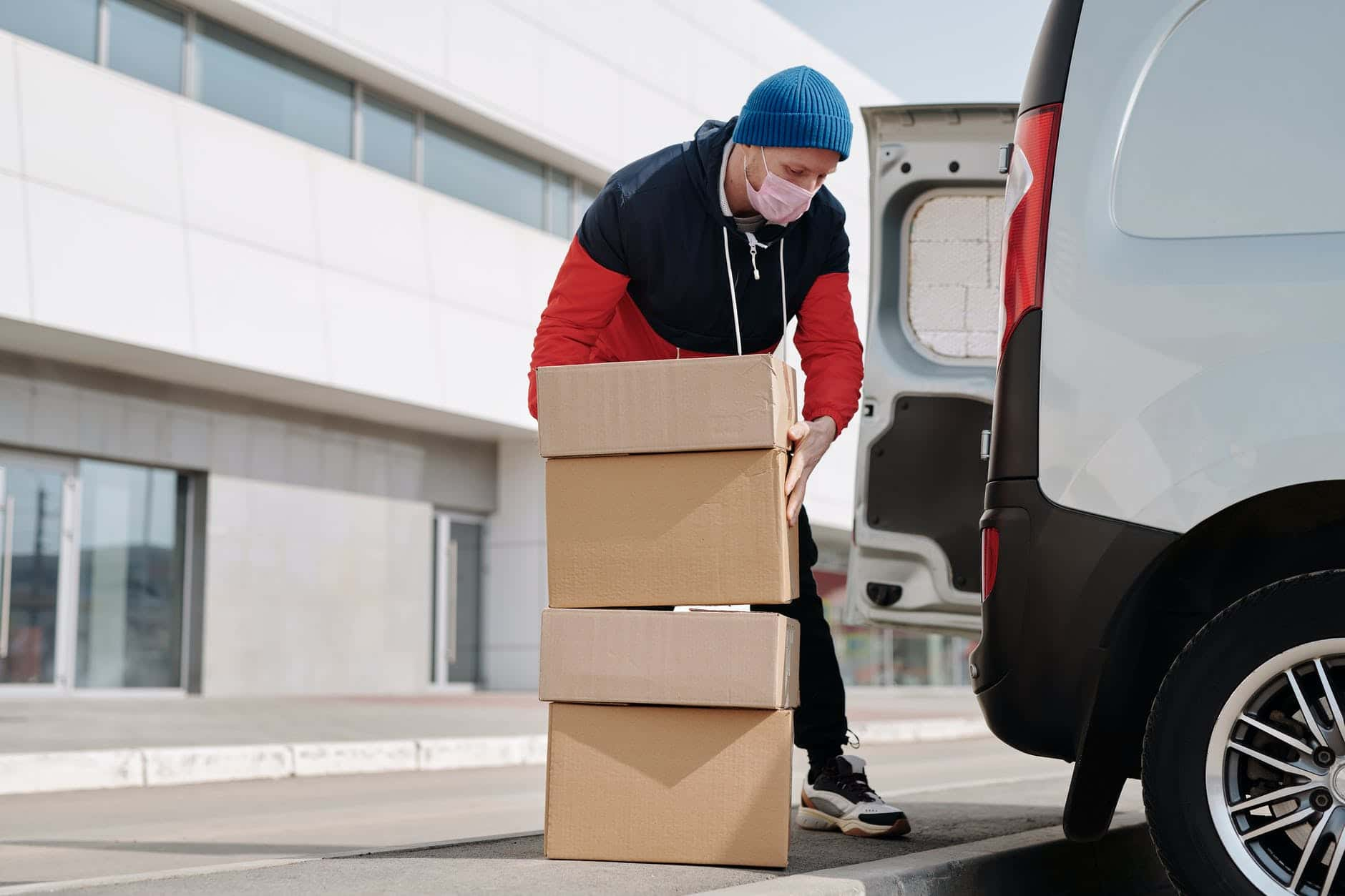 delivery man wearing a face mask carrying boxes