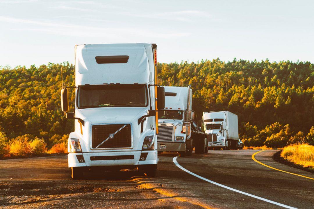 white volvo semi truck on side of road Com o avanço das soluções inteligentes em gestão de frotas, transportadoras conseguem automatizar e unificar processos, aprimorando sua logística