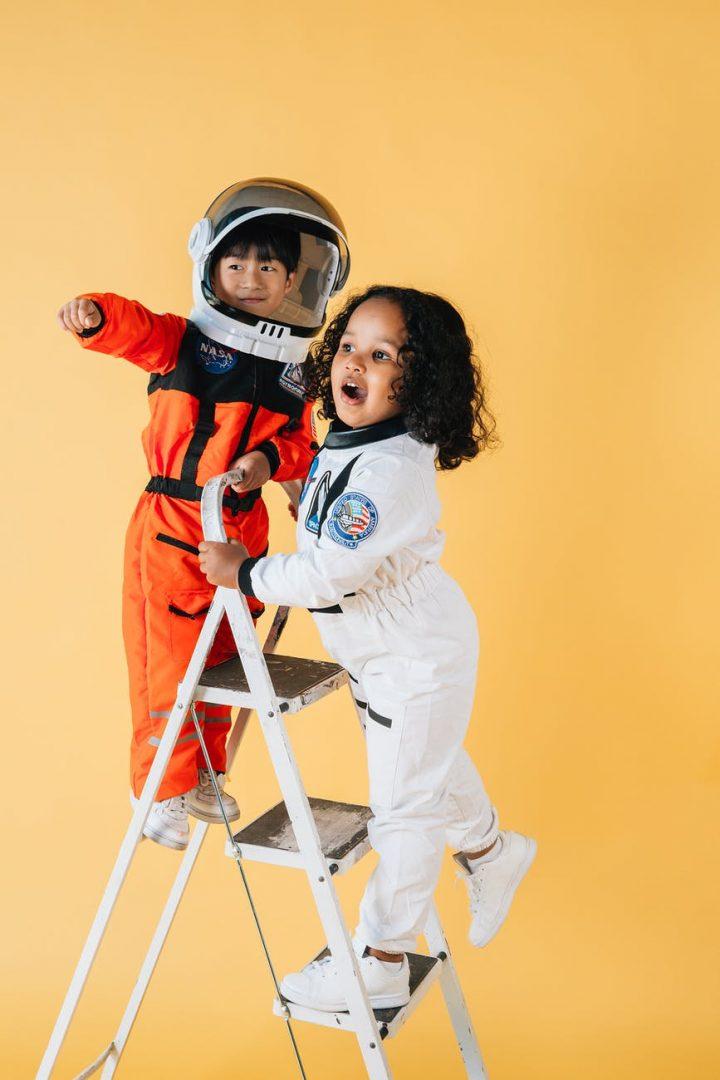 Duas crianças brincam vestidas de astronautas. Como será a infância em 2030