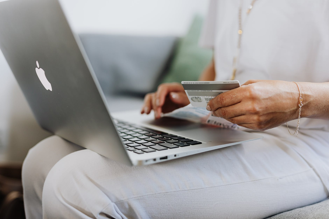 person using a macbook and holding a credit card cartao de crédito